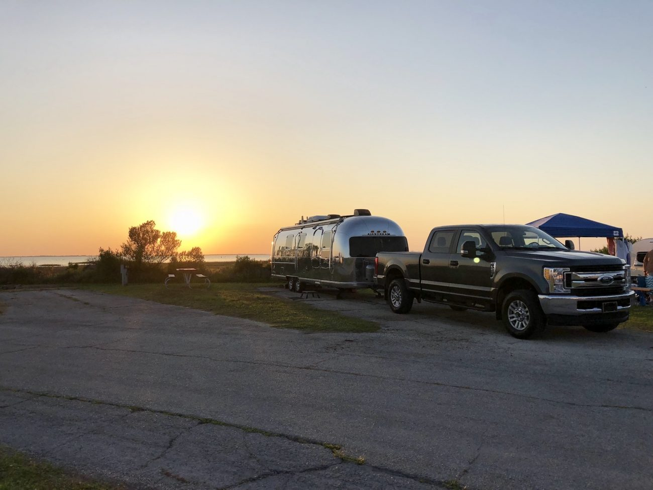 Sun goes down behind Airstream and Truck