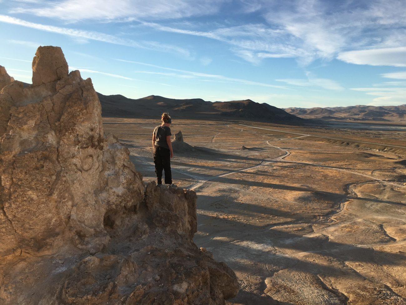 Girl on top of rock overlooking the desert