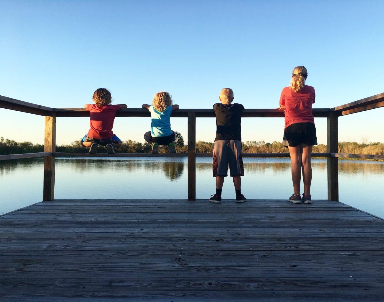 Four children overlooking pond.