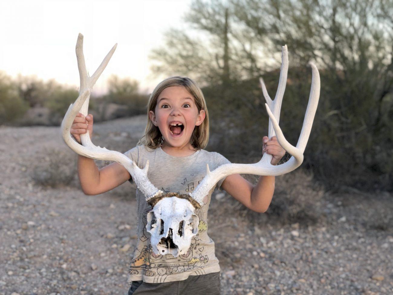 Little girl holding deer skull.