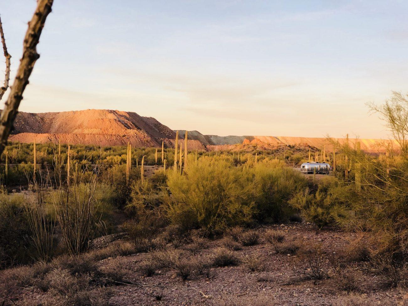 Airstream boondocking among cactus near mine at sunset in Ajo, AZ