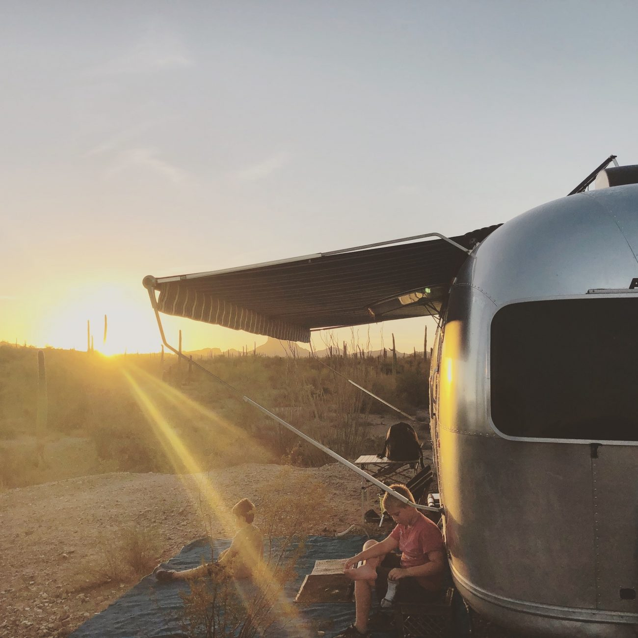 Airstream at sunset in desert with awning out.