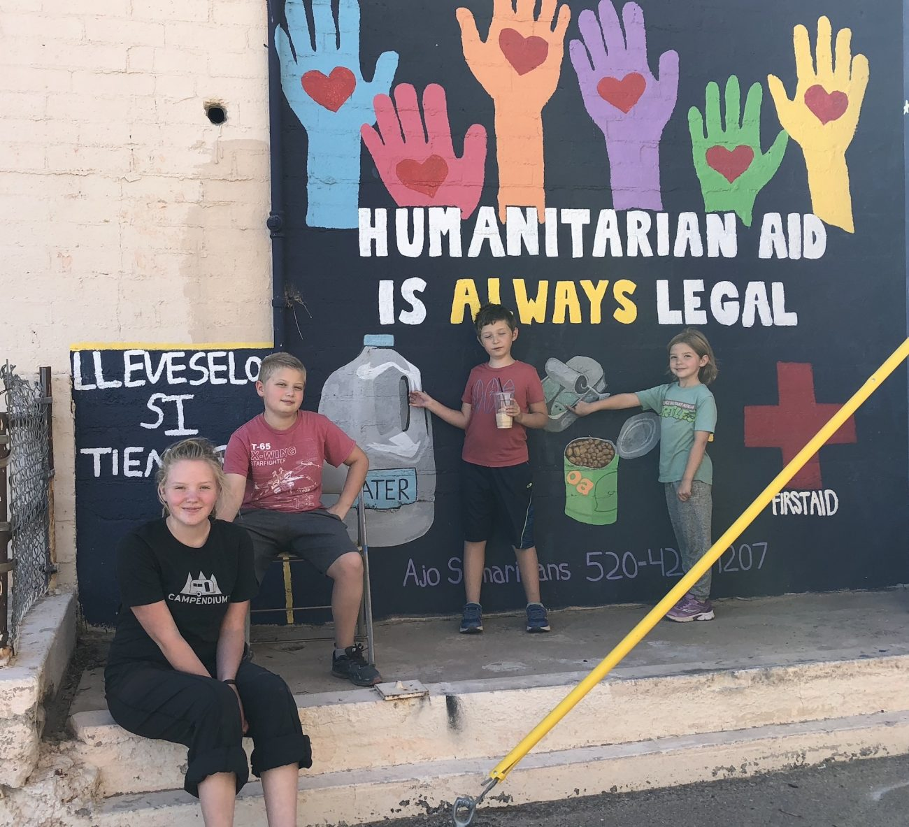 Kids standing in front of mural for humanitarian aid in Ajo, AZ.