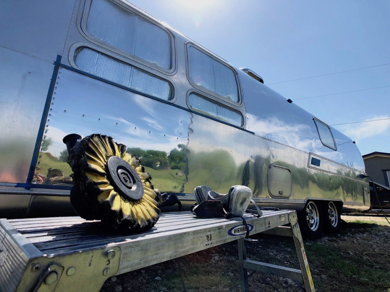 Polishing wheel in front of Airstream with a portion polished